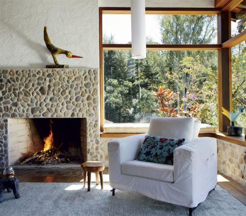 """Com a elevação do nível do piso na sala de estar, a lareira (Construfama) precisou ser completamente refeita. A moldura emprega pedras da região. """"Muito do material é de Visconde de Mauá, quando não da própria construção antiga"""", conta a arquiteta."""
