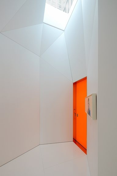 White vestibule and the phosphorescent orange elevator entry door.