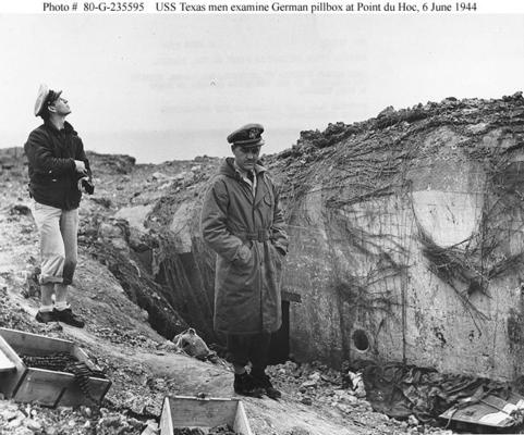"Lieutenant Commander Knapper and Chief Yeoman Cook, of USS Texas (BB-35), examine a damaged German pillbox at Pointe du Hoc on ""D-Day"", 6 June 1944. Earlier in the day Texas had bombarded the point in support of the ""Omaha"" Beach landings.The body of a dead U.S. Army Ranger, killed during the assault on Pointe du Hoc, lies covered up at right."
