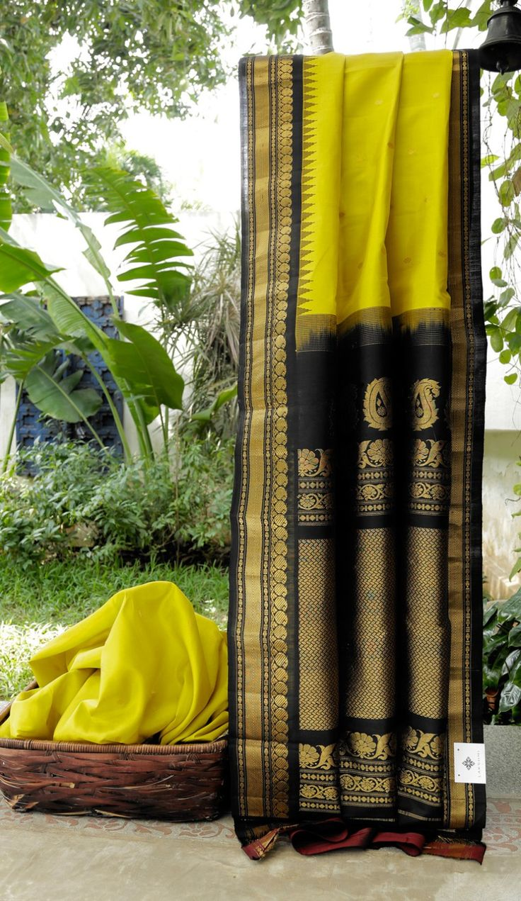 This gadwal silk has a yellow coloured body with gold zari bhuttas. The contrasting border and pallu are in oil black with intricate gold zari making it a magnificent piece