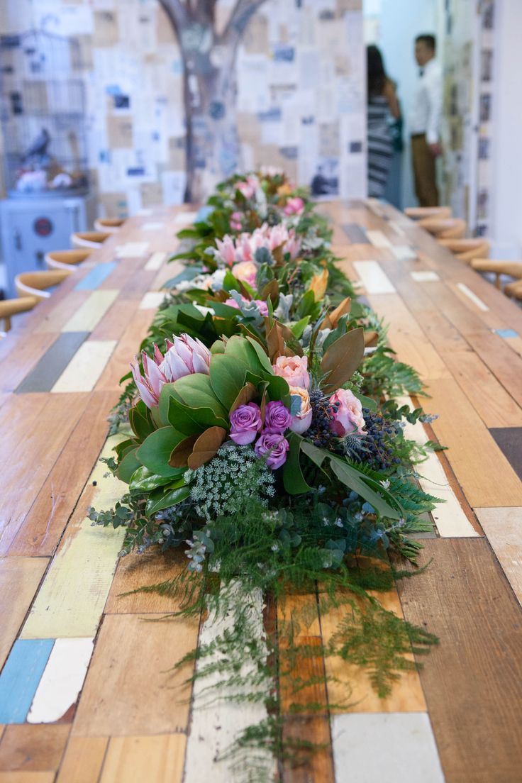 Long table arrangement for a wedding. Filled with native flowers and a few roses creating a softer look.