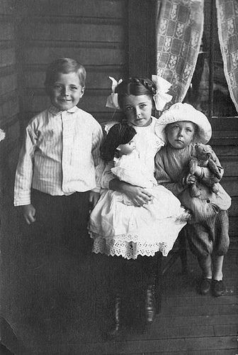 Postcard of children with a doll and a teddy bear