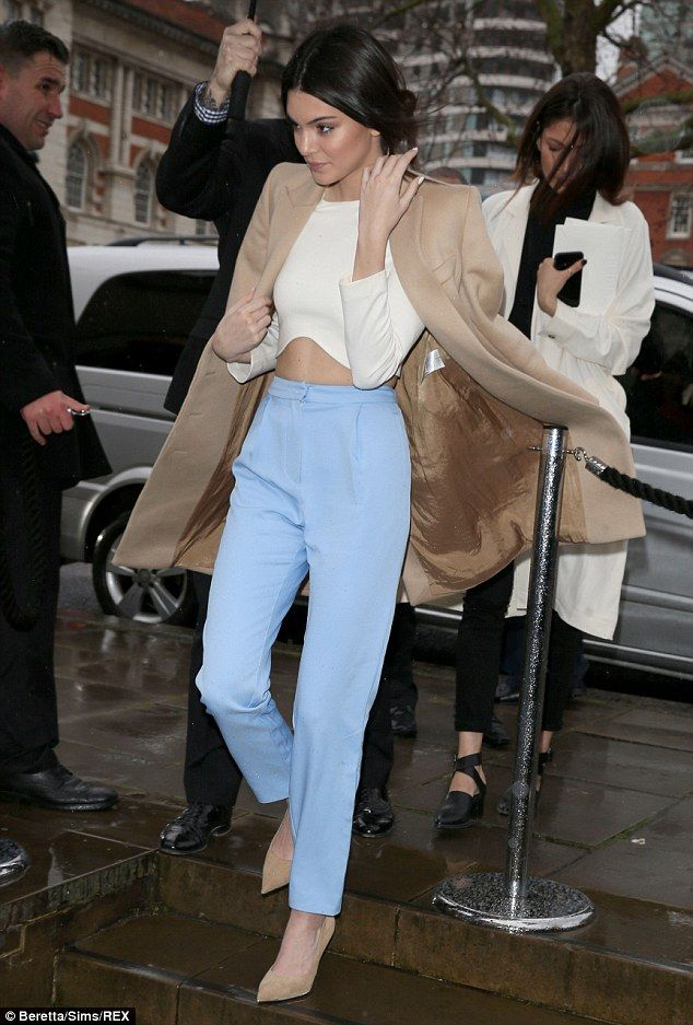 Style queen: Kendall wore a fitted pair of blue trousers with a cream crop top, capped with a camel-colored overcoat which she draped over her shoulders