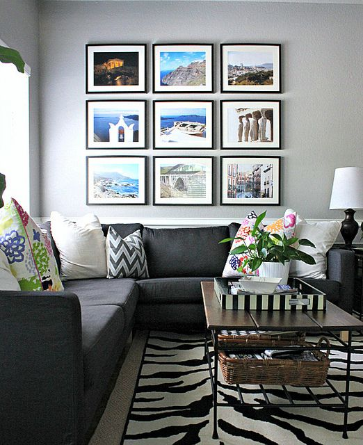 Love the drama of the large print grouping above the couch. Great colors in the photos and pillows to balance out the neutral couch, walls, and rug.