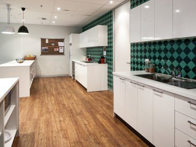 Commercial office kitchen with a warm feel enhanced by the vintage splash back tiles and timber flooring.