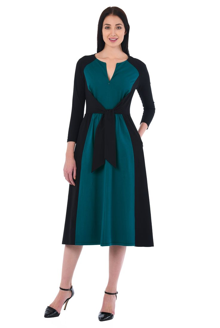 Attached side ties to the front of the elastic seamed waist adds flattering definition to our beautifully draped cotton jersey knit dress in two contrast tones.