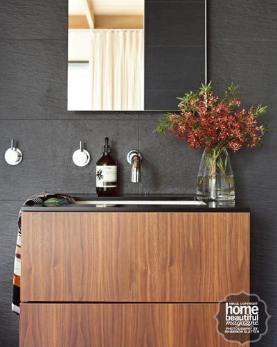 A shapely wall-hung vanity, designed by architect Peter Maddison, appears to float in this contemporary space. Its backed by large-format charcoal tiles from Signorino Tile Gallery.