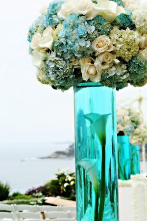 Something small like this?  Round short case with turquoise dye and White flowers? With silver votives