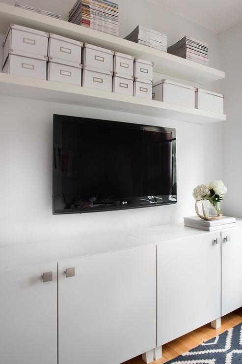 perfectly organized living room features white floating shelves mounted above a television fixed over white flat front tv cabinets pinterest organizing