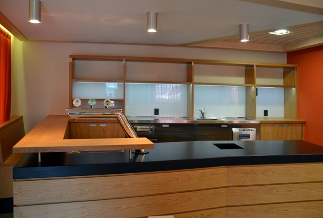 Bar counter: durmast cladding, top and sides upholstered with black zinced metal, with drinks cooling system and beer faucet. Back counter with durmast bases and shelves; glassed back and led lighting.