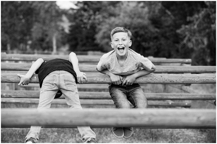 Boys brothers having fun  spontaneous moments fence family photographer Kamloops