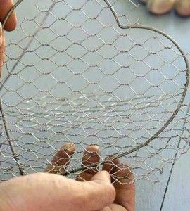 Attaching chicken wire to heart-shaped frame to create a Wire and stone heart DIY home decor craft project