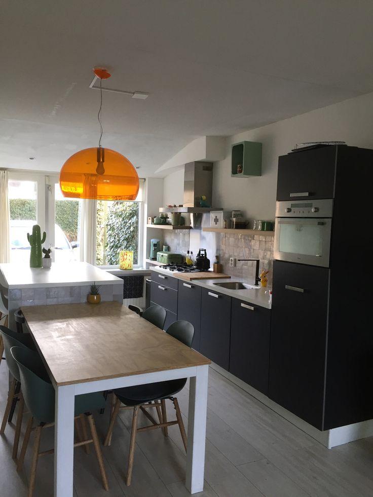 Keuken zwart wit. Keukenplanken hout. Zelliges op de muur. Oranje lamp Kartell.