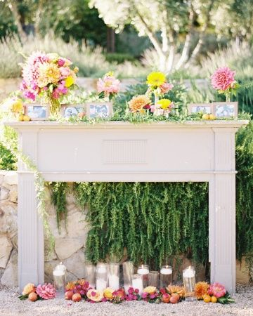In search of a unique altar idea? This couple used an antique fireplace arch decorated in flowers, vines, pillar candles, and photos