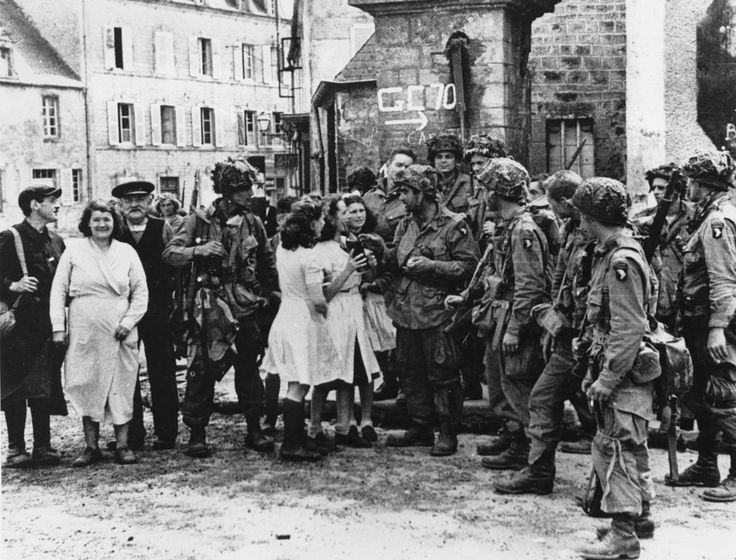 American 101st Airborne Division June 6, 1944 paratroopers of the 506th PIR, 101st Airborne meet civilians at Saint Marie-du-Mont, the planned drop zone point two miles from the German battery at Brecourt Manor. AFter clearing out the battery members of Easy Company captured the Manor while the 2nd Battalion secured St. Marie-du-Mont.