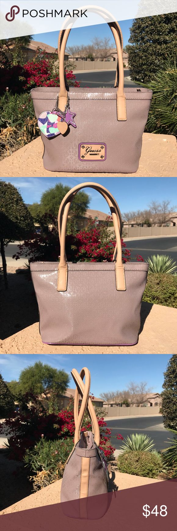 """Guess Airun Handbag Purse Taupe w/Charms Preowned GUESS Handbag is cute and versatile! MSRP $98.  12"""" W x 9"""" H x 4-1/2"""" D—Very roomy!  Handles have 8"""" drop. Zip closure, silver-tone hardware, logo exterior. Guess signature plaque has super light scratches. Decorative charms have blemish on back, as noted in photo. Colorful interior fabric in good condition; one zip pocket, 3 slip pockets.  Pre-owned condition w/light scratches and pen marks. Message me with any other questions & thank you…"""