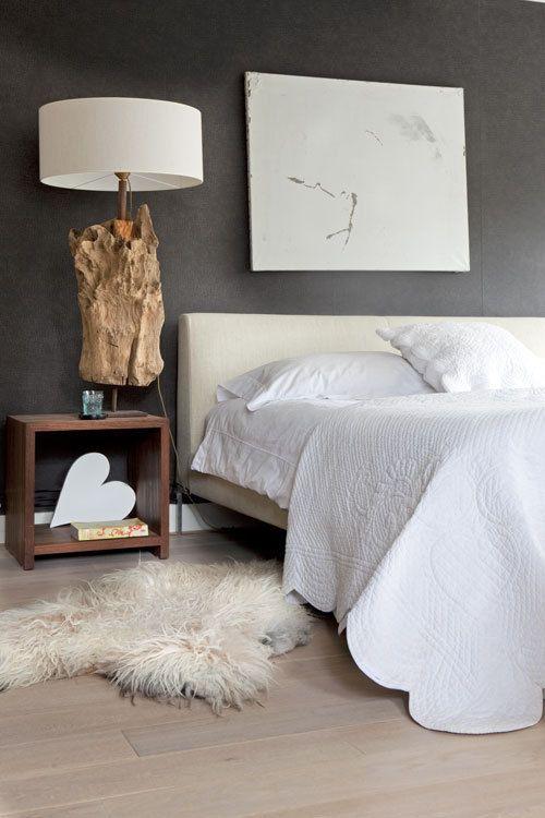 Een donkerbruine muur in de slaapkamer is best gedurfd, maar in combinatie met witte accessoires en hout kun je een heel mooi en rustig effect creëeren.