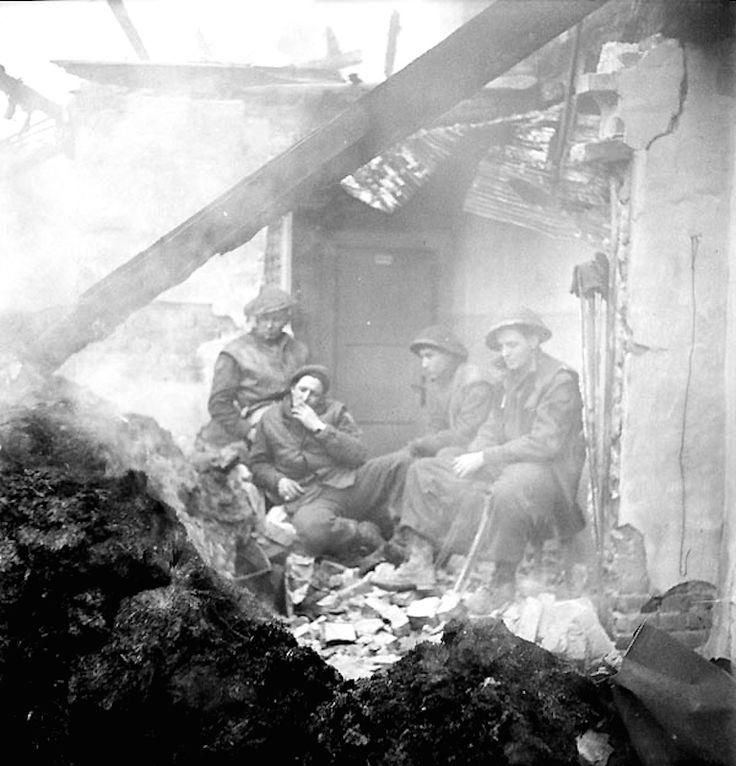 Fantassins de la Regina Rifle Regiment se réchauffent dans les ruines fumantes d'une maison, Zyfflich (Allemagne), 9 février 1945 Fantassins de la Regina Rifle Regiment se réchauffer dans les ruines fumantes d'une maison, Zyfflich (Allemagne), 9 février 1945