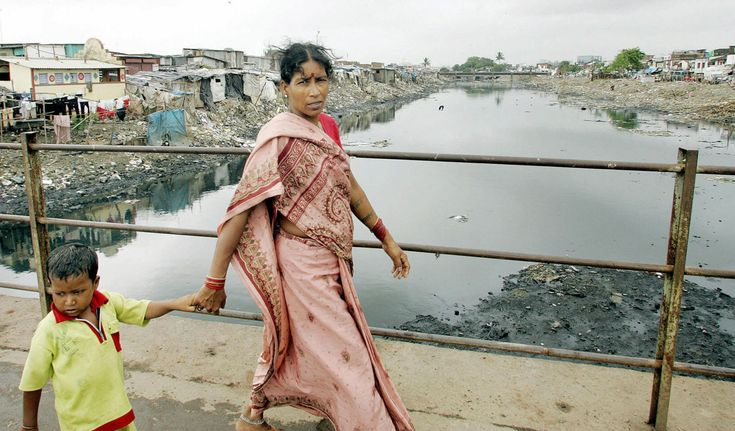 Dying Waters: India Struggles to Clean Up Its Polluted Urban Rivers.    A woman and her son cross the Mithi River in Mumbai.