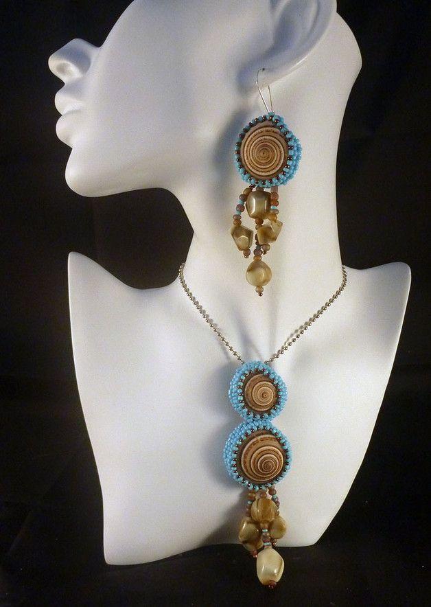 Naszyjnik wykonany metoda haftu koralikowego.  Biżuteria w odcieniach  niebieskiego i brązowego. Wymiary: dł. 50 cm , średnica wisiora 12 x 3,5 cm Koraliki: dobarwiane muszelki, szlifowane...