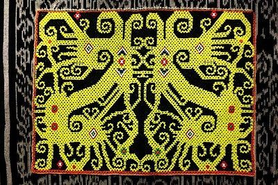 Netted beadwork panel, probably a baby-carrier sling, of the Kenyah Dayak people of Borneo. The protective creatures on the panel are said to speak, and warn the mother, if danger approaches her child.