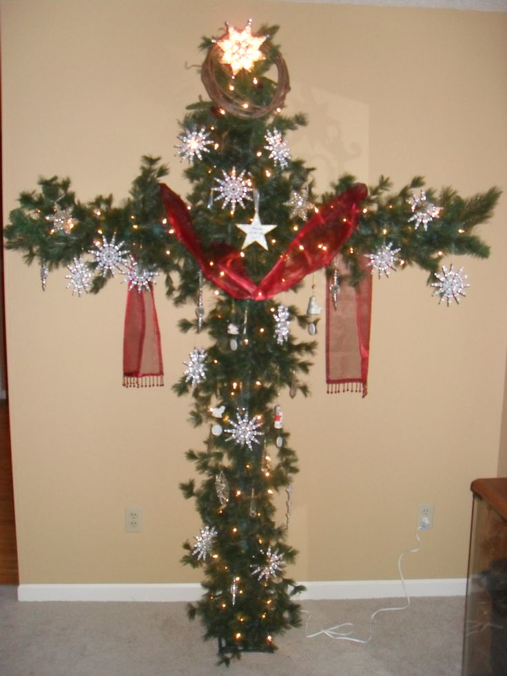 "A Cross Christmas tree.  Made from PCV pipe and garland.  Red sash symbolizes our sins and the snowflakes symbolize forgivess.   Isaiah 1:18 ""Those your sins be as scarlet,they shall be white as snow."""