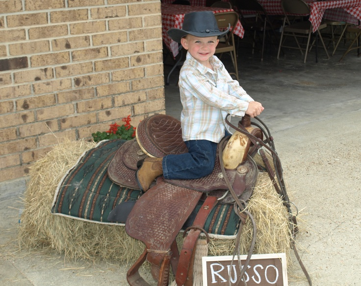 This is a picture/welcome spot from the party. We took a real saddle and put it over a bale of hay. The kids really liked sitting on it and pretending to ride a horse. I made signs out of carboard, stain and white paint pens.   # Pin++ for Pinterest #