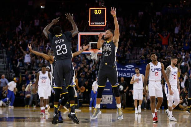 Stephen Curry of the Golden State Warriors celebrates with Draymond Green after making a threepoint shot to end the first quarter of their game...