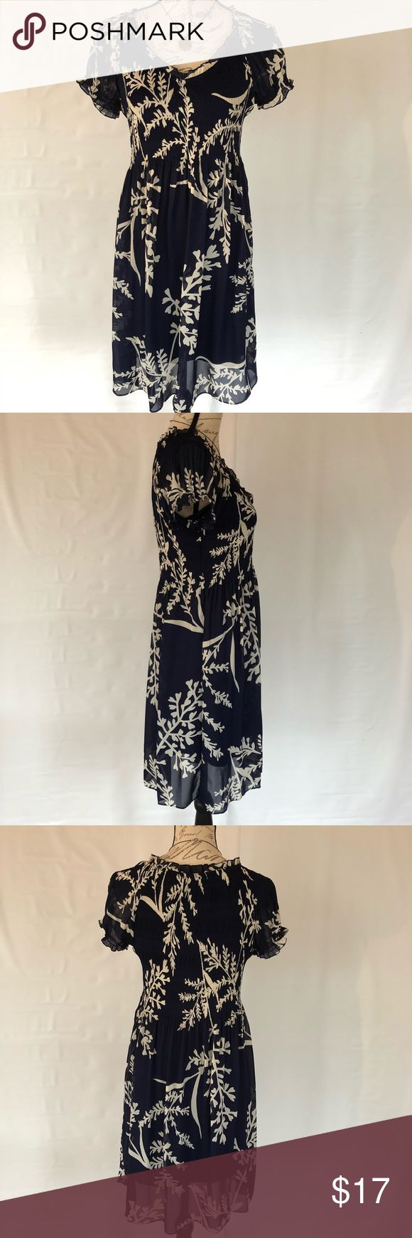 Breezy Navy and White Crinkle Stretch Frilly Dress Navy with bold white floral print. Crinkly gathered bodice with full flowy skirt, cap sleeves and v-neck all hemmed with ruffles. Fully lined polyester dress. Machine wash and dry. Great condition - only one tiny snag on shoulder (see pic). Sunny Leigh Dresses