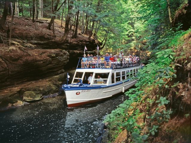 "Take the Upper Dells Boat Tour in Wisconsin Dells, Wisconsin. The tour stops at Stand Rock, the ""trademark of the Dells,"" where you will watch a trained dog leap the five-foot chasm from the main cliff to the rock ledge. The demonstration commemorates the world's first stop-action photo taken by famous Dells photographer H.H. Bennett in 1888"