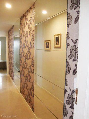 Uma circulação comprida ganhou vida com painéis de espelho e papel de parede. Os espelhos dão sensação de profundidade e o papel intercalado ajuda a diminuir a sensação de monotonia ao passar pelo corredor. Projeto de Paola Bassani Louzada.
