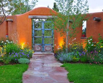 This warm-hued Southwestern-style wall plays right into the floral color scheme of golden Moonshine yarrow (Achillea sp), while the gate echoes the cool tints of catmint (Nepeta sp) and pincushion (Scabiosa sp).