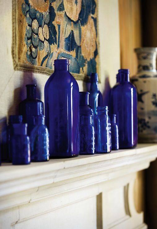Cobalt Blue Bottles - Mediterranean - living room - Atlanta Homes & Lifestyles. Plus limestone mantle and old tapestry