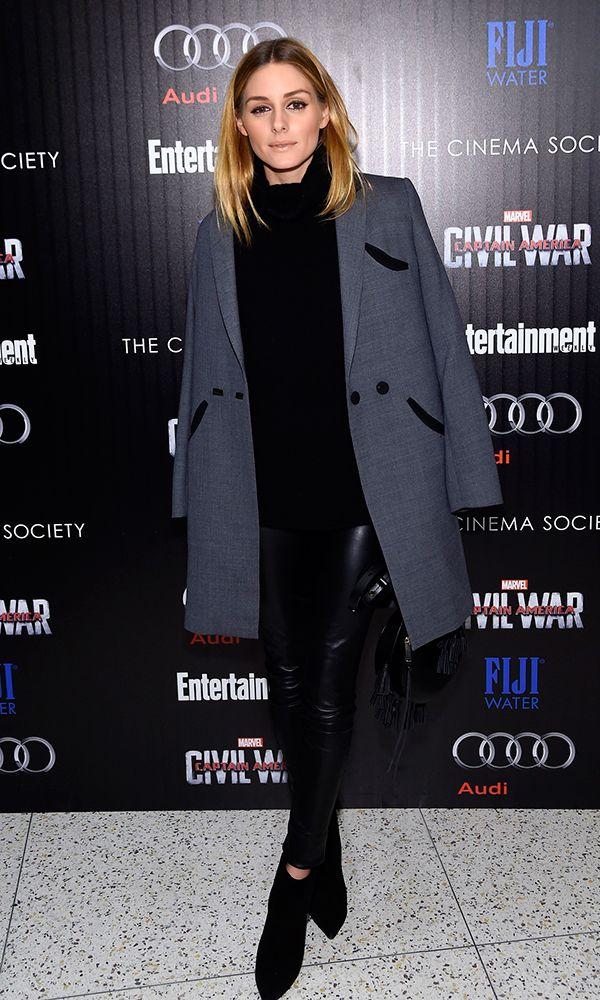 Olivia Palermo veste turtleneck preta, calça skinny de couro preta, ankle boots pretas e casaco clássico de alfaiataria cinza