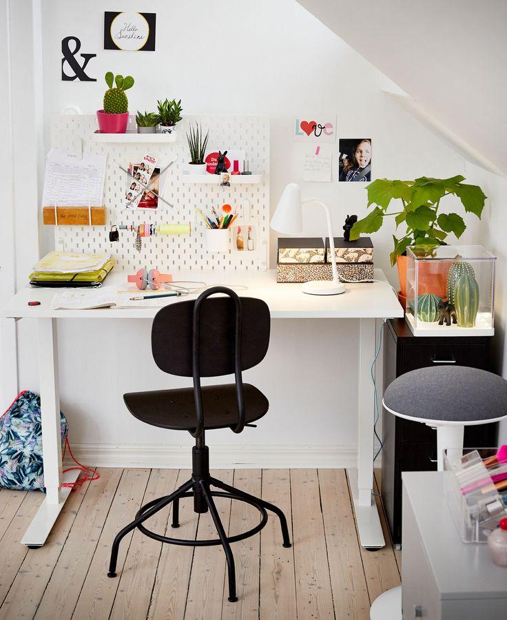 Studiehörna med vitt höj- och sänkbart skrivbord samt svart arbetsstol.