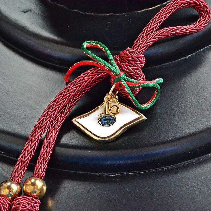 Γούρι μάτι του ώρου, που συμβολίζει την αναγέννηση, την υγεία και τη ζωτικότητα. Δεμένο με μπορντώ κορδόνι και μεταλλικά στοιχεία στο τελείωμα.
