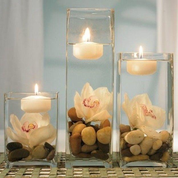 Flotantes en recipientes de vidrio de diferntes alturas completadas con piedras y flores. Ver articulo para otros arreglos.