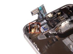 STAP 9 . Zorg ervoor dat u de kleine aarding vinger voor de camera aan de achterkant in de buurt van de power knop niet verliest. Dit vinger zit aan de bovenkant van het logic board, vastgeschroefd en bedekt met de zelfklevende zwarte plastic tape.