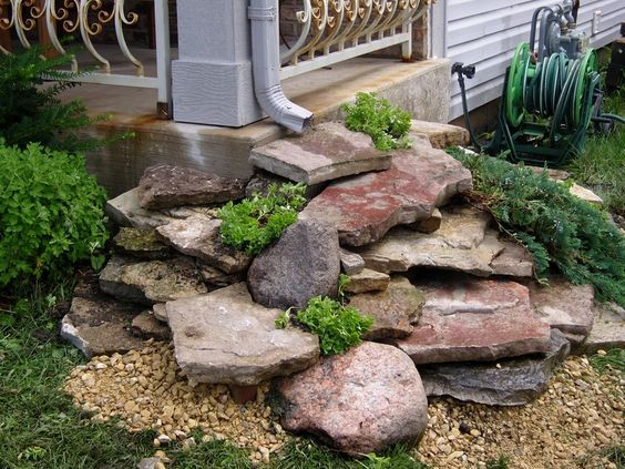 dry creek bed under waterfall at downspout
