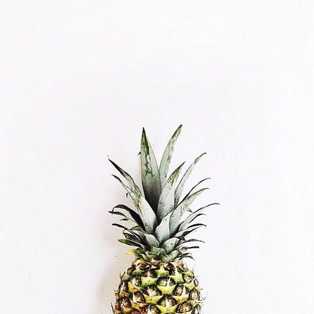 Good food photography. The pineapple is a busy fruit itself I think having it on a white wall is better than trying to use props or add a crazy background.