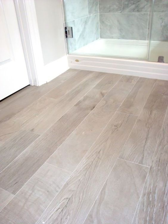 Tile wood floor with natural stone wall tiles moves the natural look throughout the entire room.