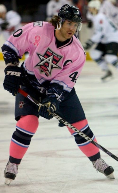 A big burly hockey player wearing pink. Awesome.