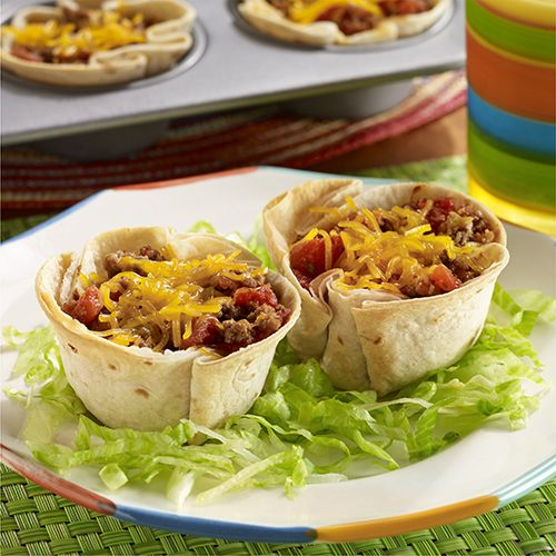 Mini bean burrito bowls made with refried beans and taco seasoned meat baked inside tortilla cups, topped with cheese and served with lettuce