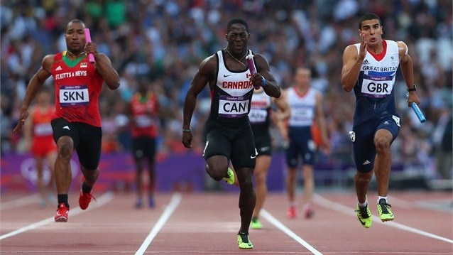 Brijesh Lawrence of Saint Kitts and Nevis, Justyn Warner of Canada and Adam Gemili of Great Britain approach the finish line during the men's 4 x 100m Relay Round 1 heats on Day 14