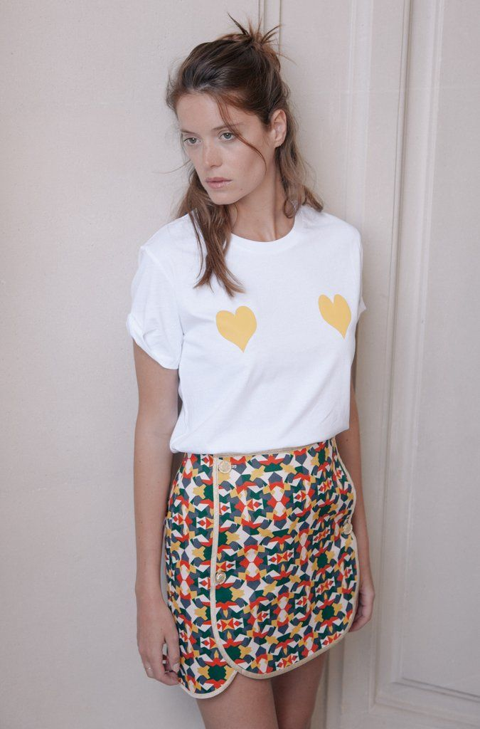 """Lucianaest une jupe en cotonà l'imprimé dessiné par Elise Chalmin, elle se porte avec un teeshirt blanc, une chemise nouée, ou un chemisier. Notre jupe a été confectionnée avec l'idée de pour la """" Mix and Match """" elle s'assemble grâce à 4 boutons dorés sur le devant, ainsi en vous offrant deux jupes de la collection vous en aurez 4 dans votre placard car la partie frontale de la jupe est amovible grâce à son assemblage à boutons ! Elle se porte avec une paire de talo..."""