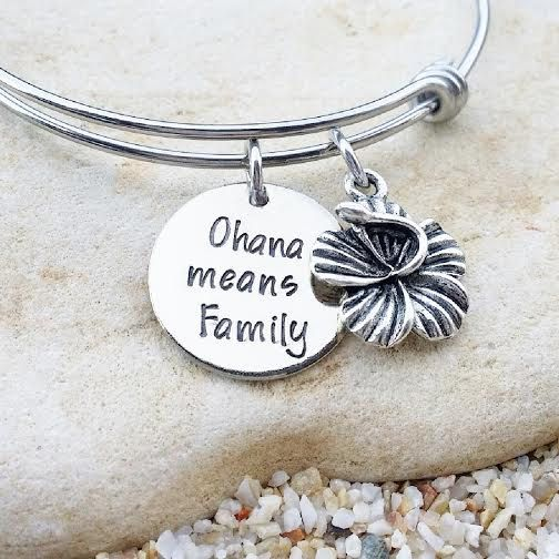 OUR STORY: At KK&Whimsy, we love incorporating personalized elements into our style! We know that each of our clients have a unique story and have walked a unique journey that ultimately created who they are at their core. Our hand stamped jewelry is a tribute to your life, your family and all the things you love.  ITEM DESCRIPTION: This Lilo and Stitch inspired bangle is made of a 3/4, 20 gauge nickel disc and is hand stamped with the phrase Ohana means Family. It is coupled with a Tibetan…