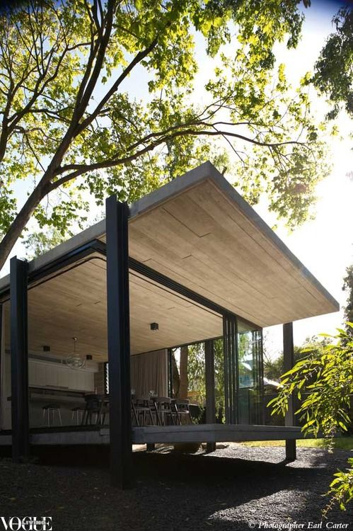 Architects EAT designed a house addition around an existing elm, abstracting the tree dominant trunk form into structural steel columns. .