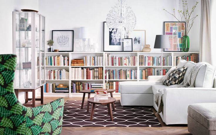 i like this look: lining up short bookcases like you've done and purposefully using tops like a mantle/counter