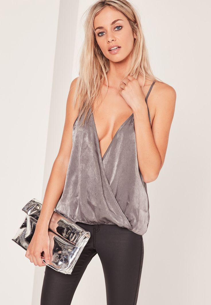 Look sleek in satin. Dare to bare in this cami top with a wrap over style and deep plunge neckline.