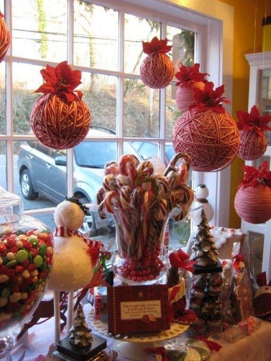 Очень необычно украшенное сладостями окно. Особенно впечатляют самодельные украшения в виде моточков из красной и белой шерсти. .